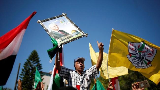 Seorang pria memegang gambar Presiden Palestina Mahmoud Abbas saat perayaan menyambut rekonsiliasi Hamas dan Fatah. (REUTERS / Suhaib Salem).