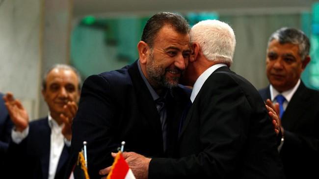 Kepala delegasi Hamas Saleh Arouri memeluk pemimpin Fatah Azzam Ahmad saat mereka menandatangani kesepakatandamai di Kairo, Mesir, 12 Oktober 2017. (REUTERS / Amr Abdallah Dalsh).