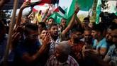 Warga Palestina merayakanrekonsiliasi demi pemerintahan bersatu setelah Hamas mengatakan bahwa mereka mencapai kesepakatan damai dengan saingannya, Fatah. (REUTERS/Suhaib Salem).