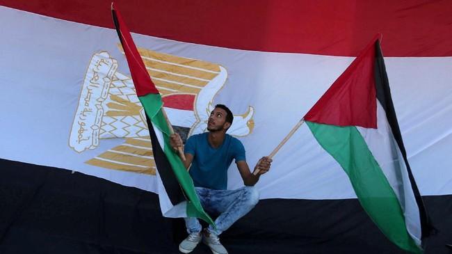 Seorang pria memegang bendera Palestinadengan latar bendera Mesirdalam perayaan setelah Hamas mencapai kesepakatan damai dengan Fatah.(REUTERS/Ibraheem Abu Mustafa).