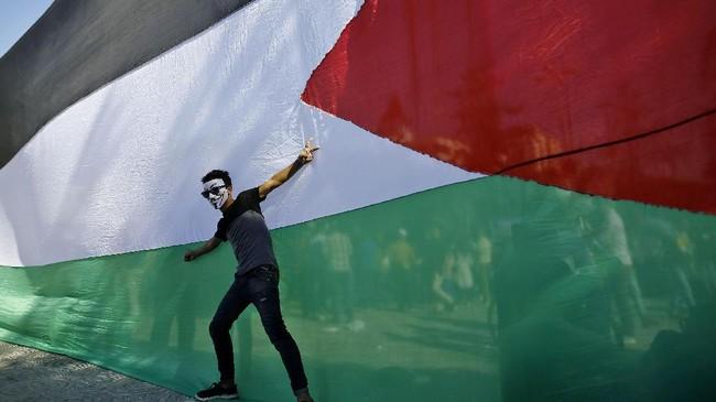 Seorang pemuda Palestina berpose di depan bendera nasionalnya selama perayaan di Kota Gaza setelah Hamas dan Fatah mencapai kesepakatan untuk mengakhiri perpecahan satu dekade. (AFP PHOTO / MOHAMMED ABED).