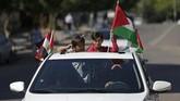 Anak-anak melihat keluar dari sebuah mobil dan mengibarkan bendera Mesir dan Palestina saat orang-orang berkumpul di Kota Gaza untuk merayakan rekonsiliasi Hamas dan Fatah. (AFP PHOTO / MAHMUD HAMS).