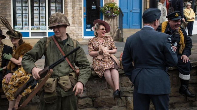 <p>Para peserta acara tersebut bukan hanya mengenakan pakaian prajurit, namun hingga berbagai karakter yang ada di masa Perang Dunia II. (AFP PHOTO / OLI SCARFF)</p>