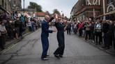 <p>Tak lupa, mereka juga merayakan acara tersebut dengan menari dan bergembira, berharap perang paling menelan korban jiwa itu tak akan pernah terjadi lagi. (AFP PHOTO / OLI SCARFF)</p>