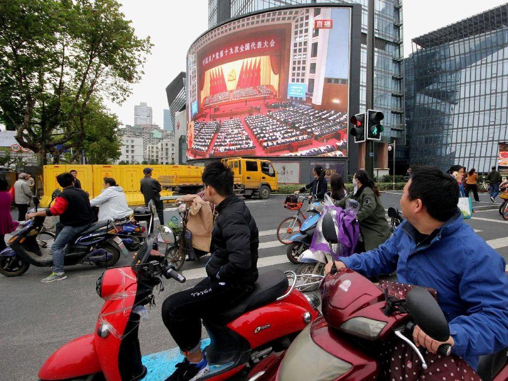 Seluruh rakyat China, bahkan yang ada di tengah jalan, mendengarkan dengan serius pidato pemimpin mereka itu. Foto: REUTERS/Stringer