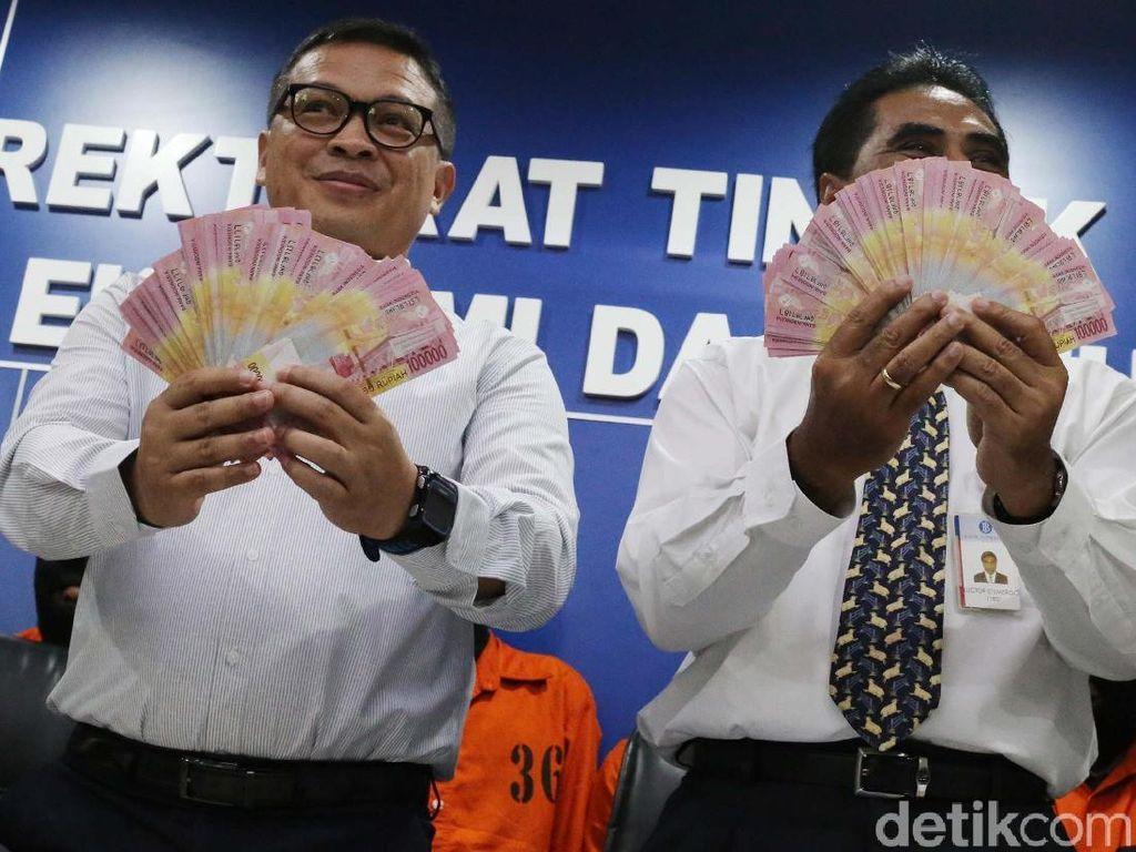 Direktur Tipideksus Bareskrim Polri Brigjen Agung Setya bersama pejabat Bank Indonesia Luctor Tapiheru menggelar barang bukti dan tersangka pemalsuan uang di Gedung Bareskrim, Gambir, Jakarta Pusat, Rabu (18/10).