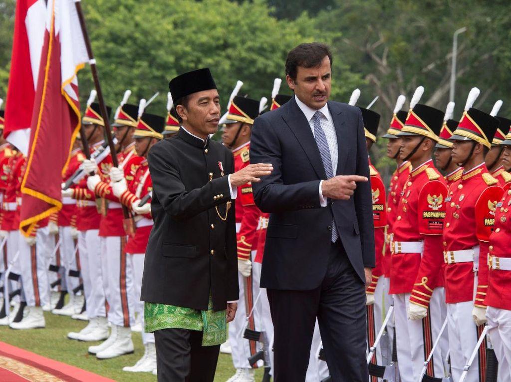Jokowi memakai baju khas Betawi dengan kain hijau sepaha, juga peci hitam. Syekh Tamim mengenakan setelan jas lengkap dengan dasi. (Foto: Reuters/Pool)