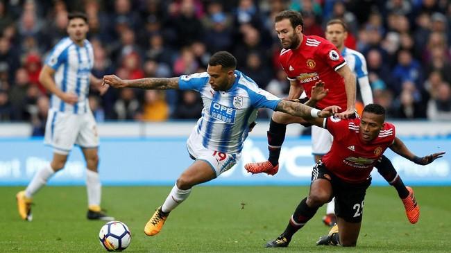 <p>Pemain Huddersfield Town Danny Williams berebut bola dengan dua pemain Manchester United Antonio Valencia dan Juan Mata. Huddersfield berhasil membuat MU kesulitan sejak awal babak pertama. (Reuters/Ed Sykes)</p>