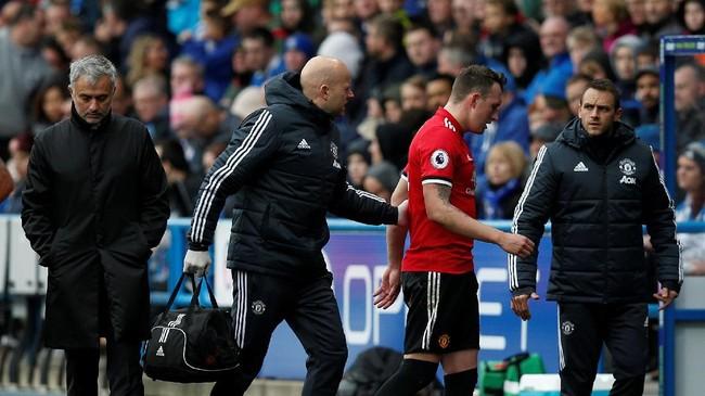 <p>Phil Jones berjalan meninggalkan lapangan melewati Jose Mourinho. The Special One kemudian memasukkan Victor Lindeloef untuk menjaga jantung pertahanan Manchester United. (REUTERS/Andrew Yates)</p>
