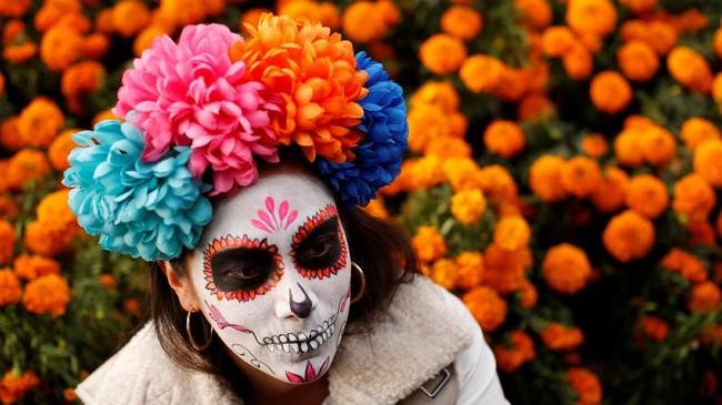 Ribuan orang memenuhi jalan-jalan di kota Meksiko untuk sebuah perayaan. Namun mereka tak menggunakan baju pesta dan berdandan cantik untuk pesta ini. (REUTERS/Carlos Jasso)