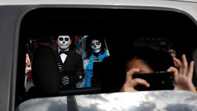 Alih-alih berdandan cantik, mereka malah justru berdandan ala hantu-hantu seram untuk merayakan Hari Orang Mati. (REUTERS/Carlos Jasso)