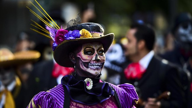 Sekilas, pesta ini mirip dengan pesta Halloween. Warga berdandan maksimal dengan kostum dan juga rias wajah yang seram.(AFP PHOTO / RONALDO SCHEMIDT)