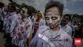 Para zombie itu melakukan aksi teatrikal menggendong pocong di jalan raya, menggeliat dan meringkuk sebagai simbol matinya kesejahteraan buruh Pertamina. (CNN Indonesia/Adhi Wicaksono).