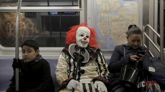 Pria mengenakan kostum badut seram 'It' menumpang kereta bawah tanah di Manhattan, Amerika Serikat. (REUTERS/Elizabeth Shafiroff)