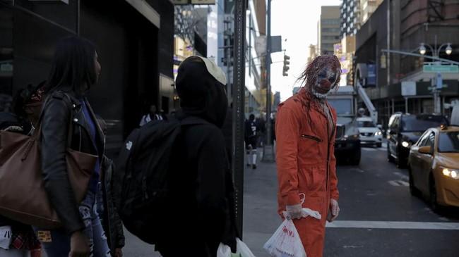 Seorang pria yang berpakaian badut seram berjalan-jalan di sekitar kawasan Times Square, Manhattan, Amerika Serikat. (REUTERS/Elizabeth Shafiroff)