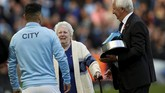 Sergio Aguero mendapat penghargaan dari legenda Manchester City Mike Summerbee (kanan) dan putri dari legenda ManCity Eric Brook, Betty Cowgill. (Action Images via Reuters/Lee Smith)