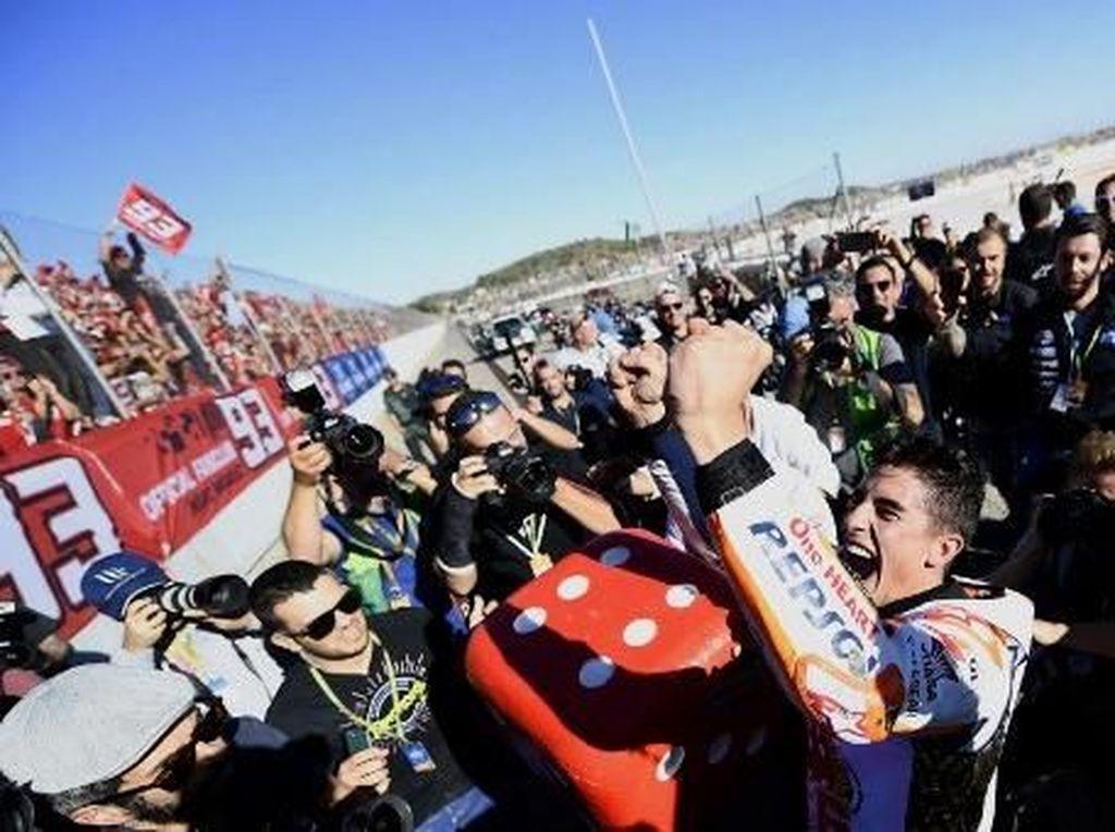 Usai balapan, Marquez langsung menghampiri tribun penonton tempat suporter setianya berada. Dia merayakan titel juaranya di sana. (AFP PHOTO / JOSE JORDAN)