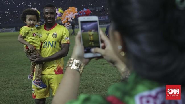 Pemain Bhayangkara FC Guy Junior melakukan selebrasi dengan melakukan selfie dengan sang anak usai pertandingan melawan Persija Jakarta. (CNNIndonesia/Adhi Wicaksono)