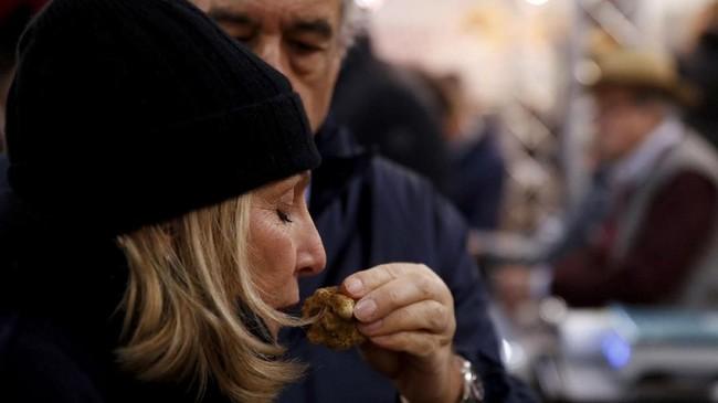 Salah satu highlight dari gelaran itu yakni lelang, yang tahun ini menjadi gelaran tahun ke-18, dengan keuntungan yang diperoleh diberikan untuk aksi amal. Seorang perempuan mencium wangi jamur truffle di pasar tradisional Alba. (REUTERS/ Stefano Rellandini)