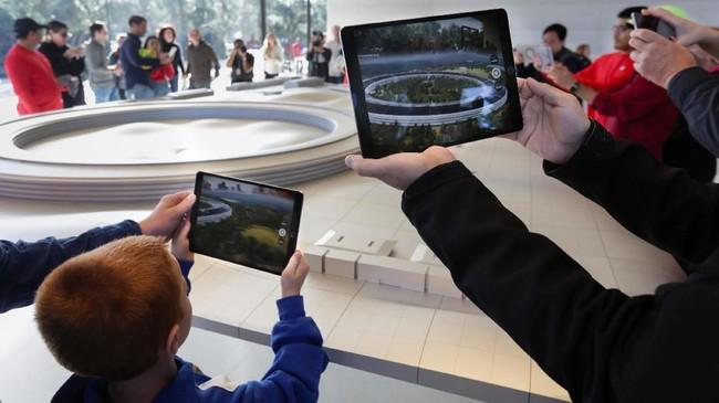 Orang tua yang membawa anak bisa mengajarkan sistem kerjabangunan berventilasi alamidan melihat salah satu instalasi energi suryamenggunakan iPad. (REUTERS/Elijah Nouvelage)