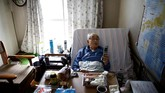 Katsuo Saito (89), pengidap leukaemia, memilih menghabiskan hari-hari tua di kediamannya di Tokyo. Suatu kali, ia dipotret saat menggunakan ponsel di atas tempat tidurnya. (REUTERS/Kim Kyung-Hoon)