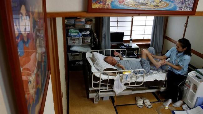 Mitsuru Niinuma (69), pengidap kanker paru-paru juga memilih berada di rumah. Ia dirawat atau dipijat terapisnya di rumah dengan kamar yang didekorasi puzzle. (REUTERS/Kim Kyung-Hoon)