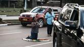 Seorang perempuan berlutut di atas bendera Zimbabwedi jalanan di Harare, Zimbabwe, pasca pengunduran diri Presiden Robert Mugabe, Selasa (21/11). (AFP PHOTO/MARCO LONGARI)