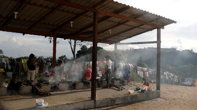 <p>Anggota Suku Waraomemasak bersama di penampungan di Pacaraima, Roraima, Brasil.(REUTERS/Nacho Doce)</p>