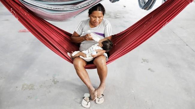 <p>Perempuan Suku Warao memberikan susu botol kepada bayinya di Pacaraima, Roraima, Brasil. (REUTERS/Nacho Doce)</p>