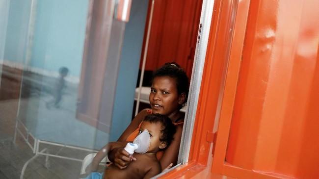 <p>Seorang anak Suku Warao sedang diterapi bersama ibunya dipenampungan diPacaraima, Roraima, Brasil. (REUTERS/Nacho Doce)</p>