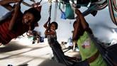 <p>Anak-anak SukuWarao bermain hammocksdi Pacaraima, Roraima, Brasil. (REUTERS/Nacho Doce)</p>