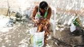 <p>Perempuan SukuWarao memandikan anaknya dalam sebuah ember di Pacaraima, Roraima, Brasil. (REUTERS/Nacho Doce)</p>
