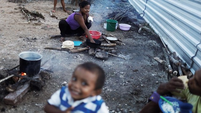 <p>Perempuan Suku Warao memasak di sebelah tenda di Pacaraima, Roraima, Brasil. (REUTERS/Nacho Doce)</p>