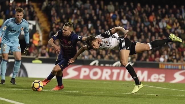 Bek Barcelona Jordi Alba (tengah) berebut bola dengan bek Valencia Gabriel Paulista dalam pertandingan La Liga di Stadion Mestalla, Minggu (26/11). (AFP PHOTO / JOSE JORDAN)