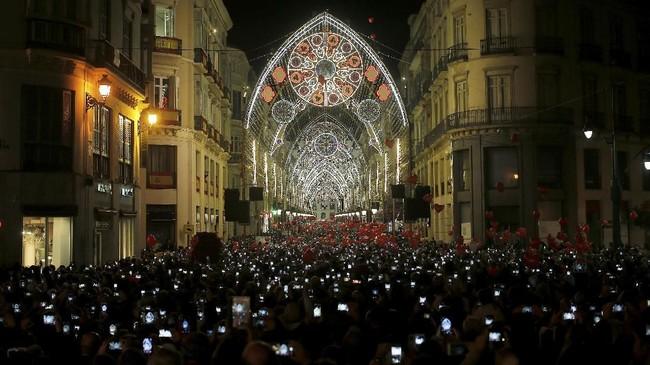 Pengunjung mengarahkan kamera telepon genggamnya saat lampu penanda datangnya Natal dinyalakan di kawasan Marques de Larios, Malaga, selatan Spanyol.(REUTERS/Jon Nazca)