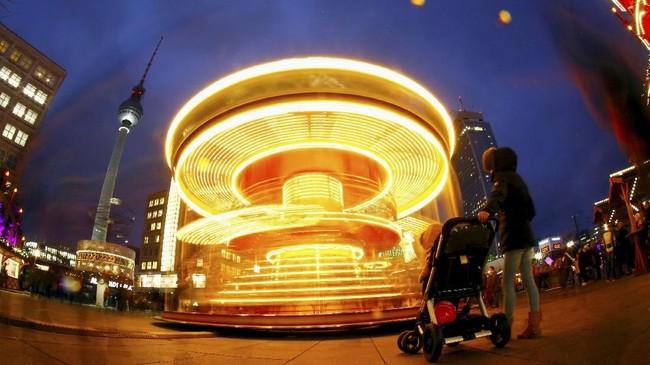 Komidi putar yang berada di kawasan Alexanderplatz, Berlin, Jerman, juga diramaikan oleh turis yang ingin berfoto di tengah suasana musim dingin romantis.(REUTERS/Hannibal Hanschke)