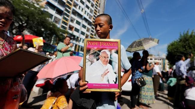 Kunjungan Paus Fransiskus ke Myammar, pemimpin umat Katolik dunia pertama yang mengunjungi negeri dengan mayoritas beragama Buddha tersebut, mendapat sambutan hangat. Seorang anak laki-laki memanfaatkan kesempatan itu dengan berjualan foto Paus Fransiskus di luar Gereja Katedral Santa Maria di Yangon, Myanmar, Kamis (30/11). (REUTERS/Jorge Silva)
