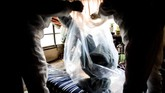 Dalam potret yang diambil 19 Agustus lalu, seorang petugas tampak membersihkan ruangan dengan pakaian pelindung. Ia memasuki apartemen pria yang meninggal sendirian tiga pekan setelah perkiraan waktu ia tiada. (AFP PHOTO / BEHROUZ MEHRI)