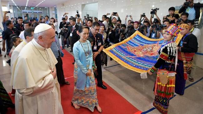 Paus Fransiskus dan Penasihat Negara Myanmar, Aung San Suu Kyi saat akan menghadiri pertemuan dengan masyarakat sipil dan kalangan diplomatik di Ibu Kota Naypyitaw, Myanmar, Selasa (28/11). Selama lawatannya di Myanmar, Paus Fransiskus menghindari kata 'Rohingya' untuk menjaga perasaan warga setempat. (Osservatore Romano/Handout via Reuters)