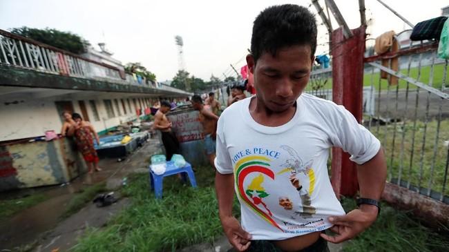 Seorang warga Myanmar mengenakan kaus peringatan lawatan Paus Fransiskus ke Myanmar di kamp orang-orang yang bepergian dari Kachinke Stadion Sepak Bola Bogyoke Aung San, sambil menanti misa Paus Fransiskus di Yangon, Selasa (28/11). (REUTERS/Jorge Silva)