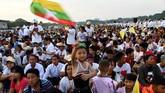 Seorang bocah melambaikan bendera Myanmar sambil menantikan kedatangan Paus Fransiskus yang akan memimpin misa di Stadion Sepak BolaKyite Ka San,Yangon, Myanmar, Rabu (29/11). Lautan manusia menyambut kehadiran Paus Fransiskus, pemimpin umat Katolik dunia pertama yang berkunjung ke Myanmar. (AFP PHOTO/Vincenzo PINTO)