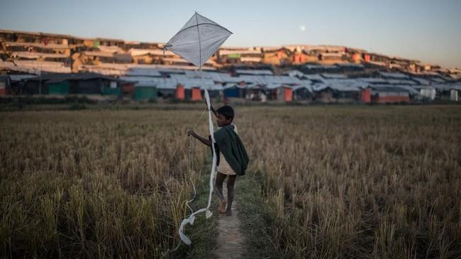 Seorang bocah Rohingya bermain layang-layang di kamp pengungsi Thankhall, Cox's Bazar, Sabtu (2/12).(AFP PHOTO / Ed JONES)