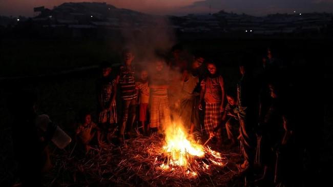 Anak-anak Rohingya bermain di depan api unggung di pemukiman pengungsi Jamtoli, dekat Cox's Bazar, Bangladesh, 24 November 2017. (REUTERS/Susana Vera TPX IMAGES OF THE DAY)