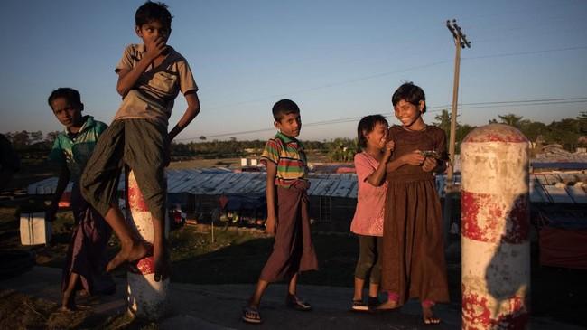 Anak-anak pengungsi Rohingya bermain di tepi jalan kamp pengungsi Shamlapur, Cox's Bazar, Bangladesh, 1 Desember 2017 lalu. Sekitar 620 ribu etnis Rohingya mengungsi ke Bangladesh sejak Agustus dan terus mengalir meski kesepakatan pemulangan mereka telah diteken bersama Myanmar. (AFP PHOTO / Ed JONES)