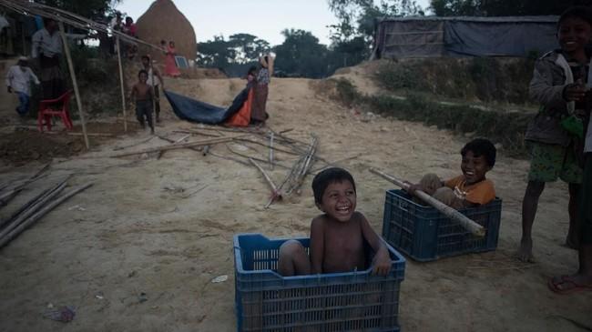 Tawa anak-anak Rohingya di kamp pengungsi Naybara, Cox's Bazar, Bangladesh, Senin (3/12). Pengungsi Rohingya terus mengalir ke Bangladesh meski kesepakatan untuk memulangkan mereka ke Rakhine telah diteken bersama Myanmar. (AFP PHOTO / Ed JONES)