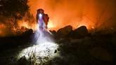 <p>Api yang sama sekali belum bisa ditangani ini ditiup oleh angin Santa Ana yang datang tanpa diperkirakan, bertiup dari arah gurun California. (AFP Photo/Ringo Chiu)</p>