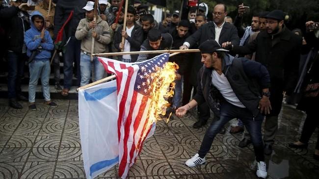 <p>Kabar soal rencana Trump untuk mengakui Yerusalem sebagai Ibu Kota Israel telah tersiar sejak Jumat pekan lalu. Saat kepastian soal itu hanya menunggu waktu, warga Palestina melampiaskan kemarahannya dengan membakar bendera AS dan Israel, foto Trump dan PM Benjamin Netanyahu. (REUTERS/Mohammed Salem)</p>