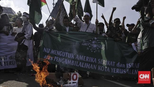 Selain membentangkan spanduk kecaman terhadap AS, peserta unjuk rasa juga melakukan aksi bakar ban.(CNN Indonesia/Adhi Wicaksono).