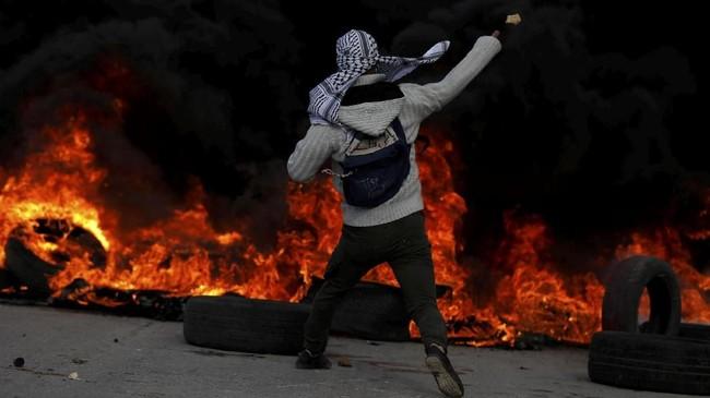 Sementara warga ini melemparkan batu ke arah pasukan Israel di lokasi yang sama. (REUTERS/Mohamad Torokman)