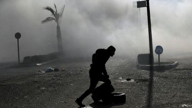 Demonstran warga Palestina ini berlari menyelamatkan diri di tengah bentrokan di dekat permukiman Yahudi di Beit El, dekat Ramallah. (REUTERS/Mohamad Torokman)